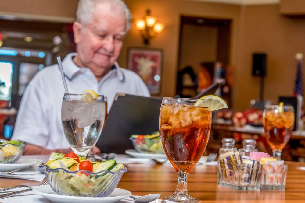 A senior looking over a menu at Watercrest at Kingwood in Kingwood, Texas