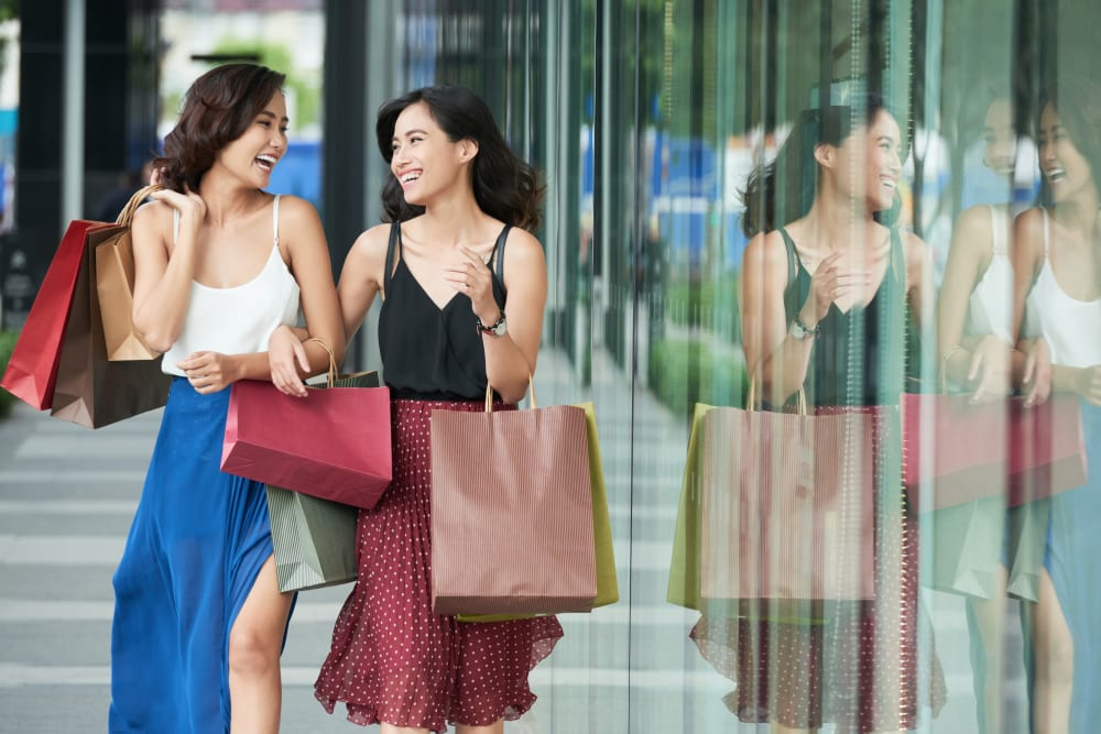 Two women walking in the city with shopping bags near The 450 in Lombard, Illinois