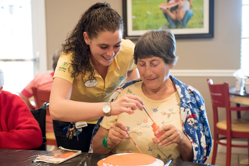 Team member and resident working on a project together at Inspired Living Sarasota in Sarasota, Florida