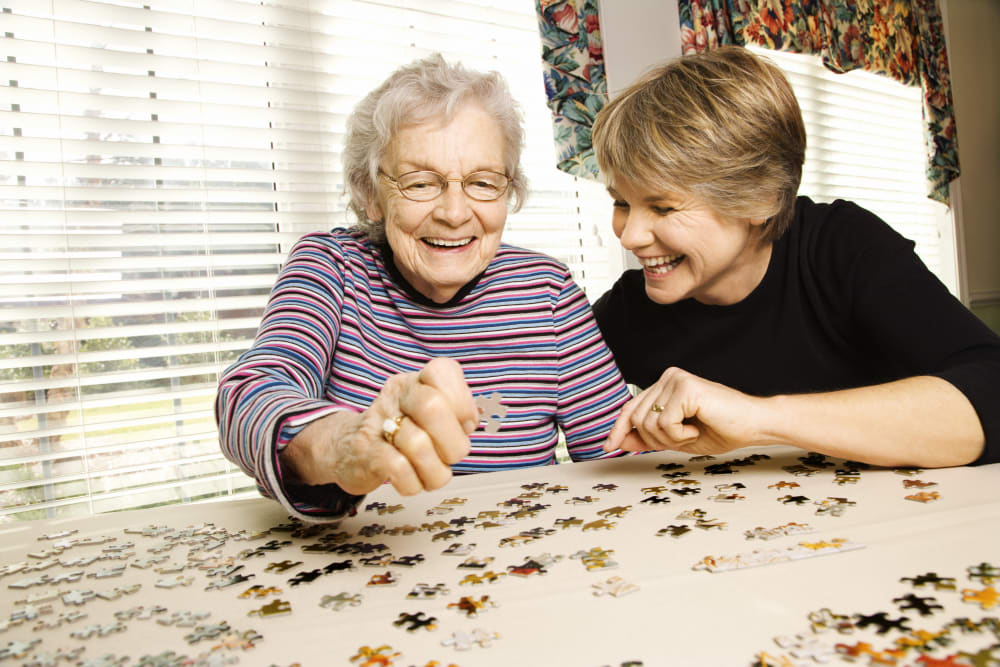 Holden of Bellevue resident doing a puzzle with a family member in her apartment in Bellevue, Washington