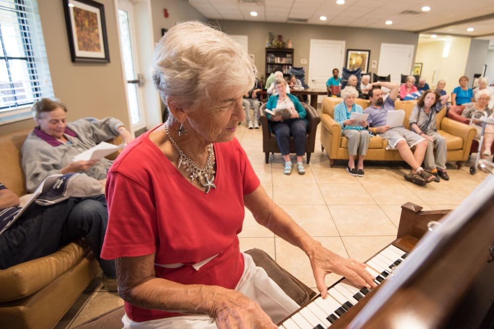 A resident playing a piano at Inspired Living Royal Palm Beach in Royal Palm Beach, Florida.