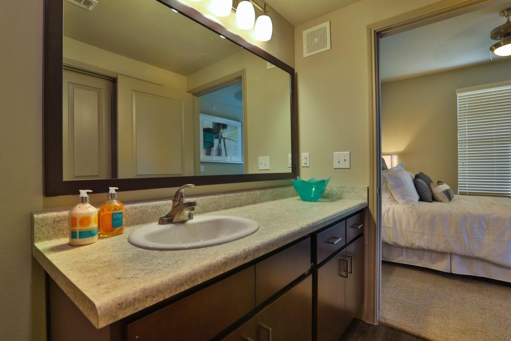 Well-lit en suite bathroom in a model home at Olympus at Waterside Estates in Richmond, Texas