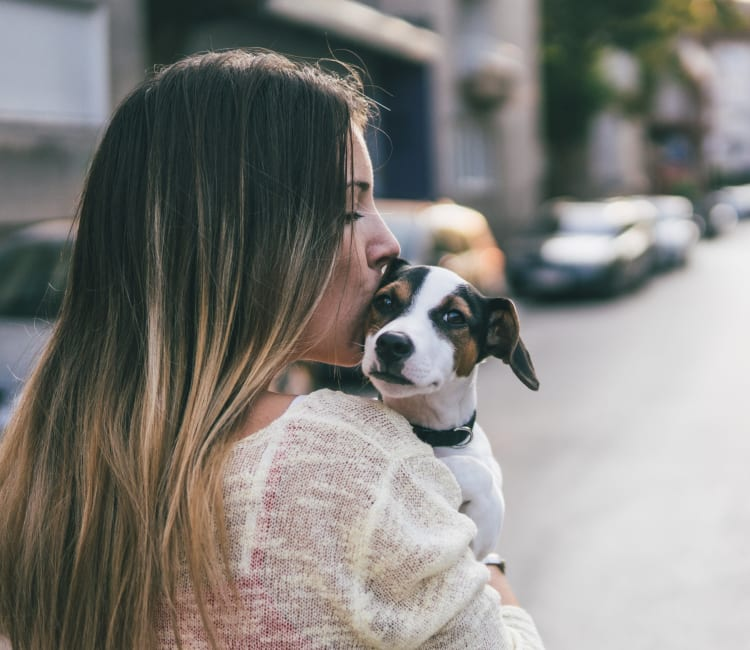 Resident giving her puppy a kiss outside their new home at Sofi Highlands in San Diego, California