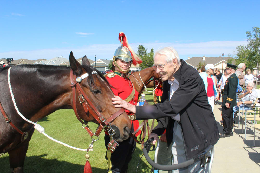 A resident petting a horse at Touchmark on Saddle Drive in Helena, Montana