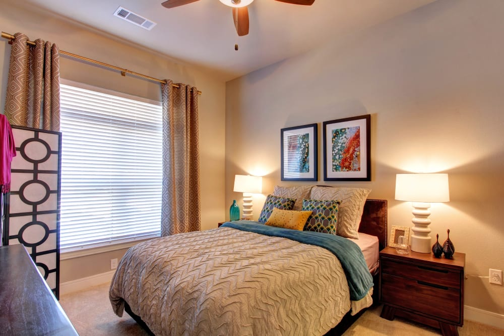 Carpeted bedroom with large window at Marquis at Barton Trails in Austin, Texas