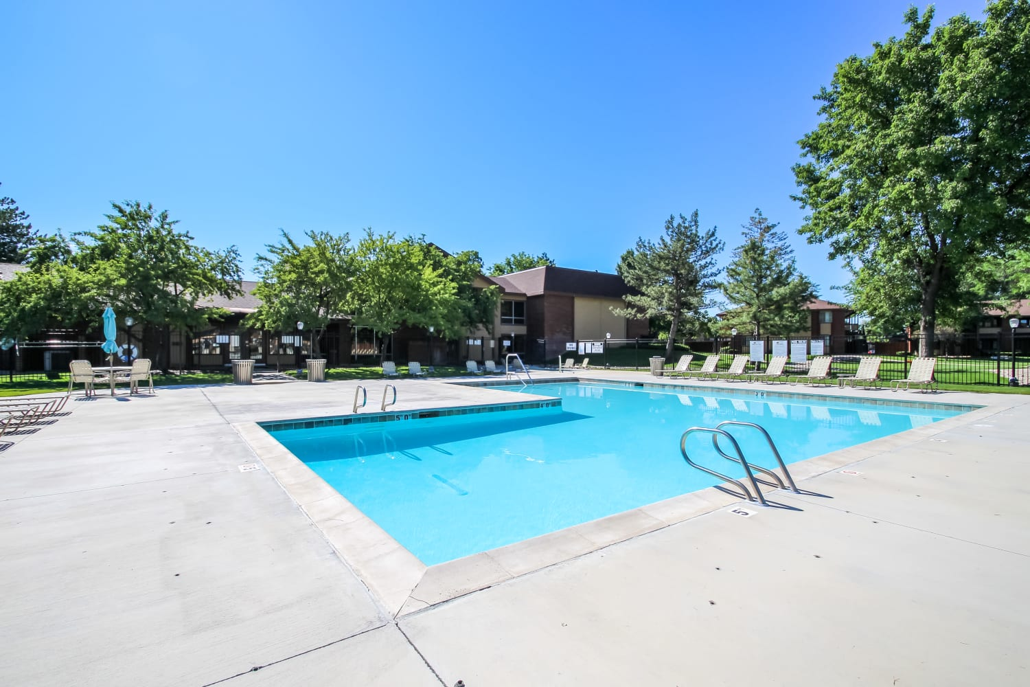 Swimming pool surrounded by trees at Wasatch Club Apartments in Midvale, Utah