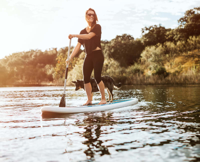 Resident and her dog on a stand-up paddleboard near Rockbrook Creek in Lewisville, Texas