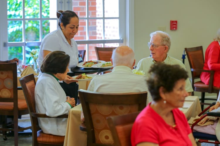 Residents being served dinner in the dining room at Harmony at Hope Mills in Fayetteville, North Carolina