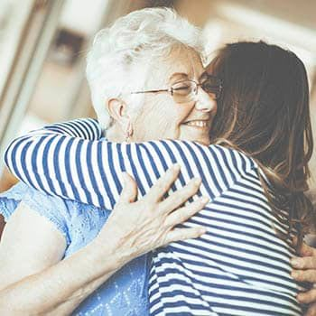 Resident and family member hugging at Brookstone Suites of Effingham in Effingham, Illinois.