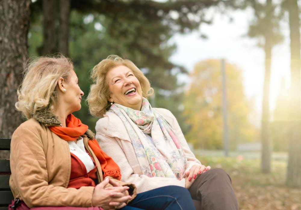Residents sitting on a bench outside of Autumn Grove Cottage at The Woodlands in The Woodlands, Texas