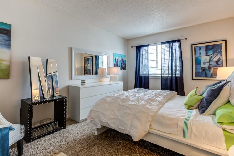 Well-decorated bedroom with plush carpeting in a model home at Stratus Townhomes in Westminster, Colorado