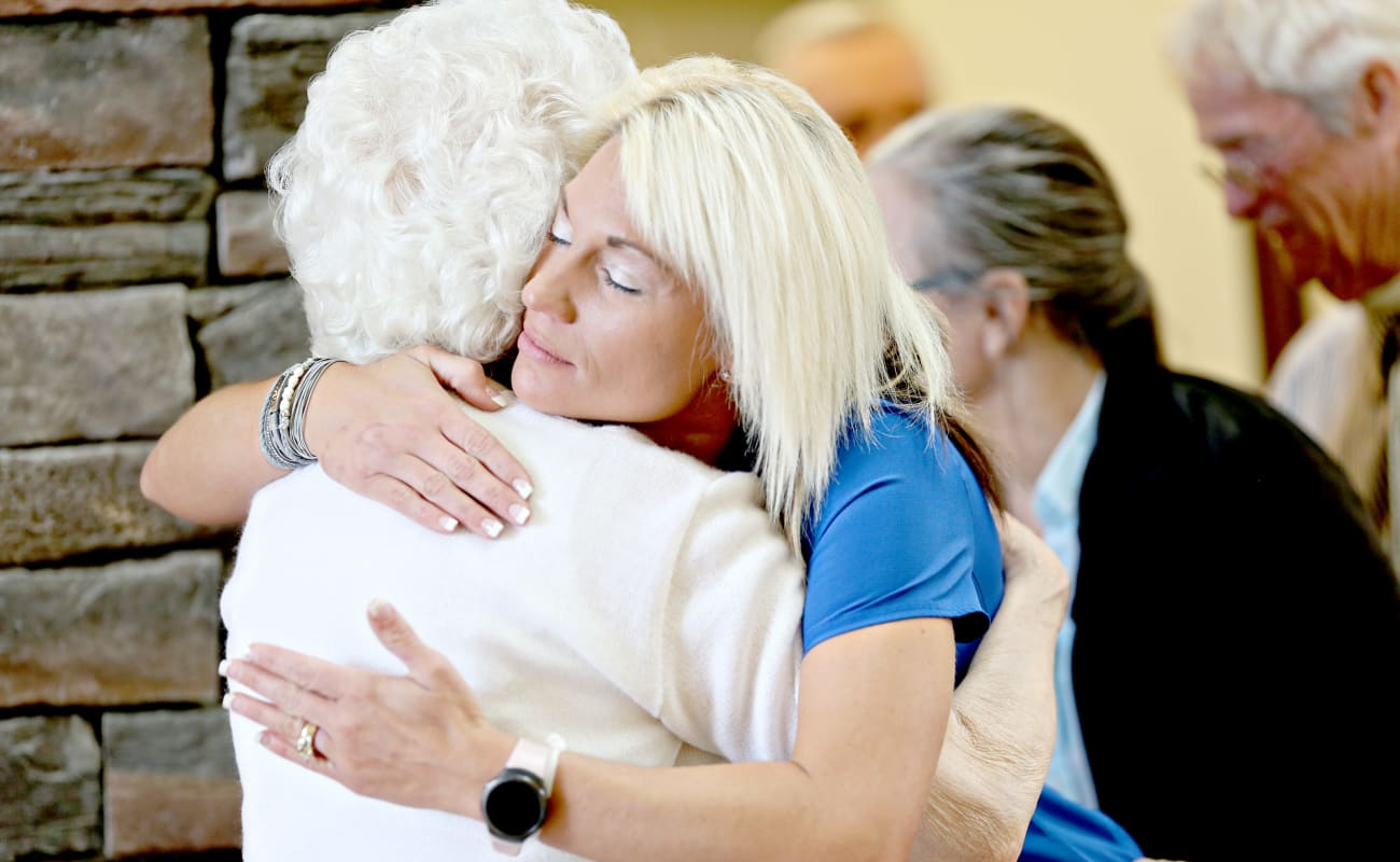Resident and caretaker embracing in a hug at Providence Assisted Living in Clarksville, Arkansas.