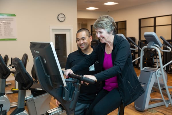 A caretaker assisting a resident with an exercise machine at Touchmark at Wedgewood in Edmonton, Alberta