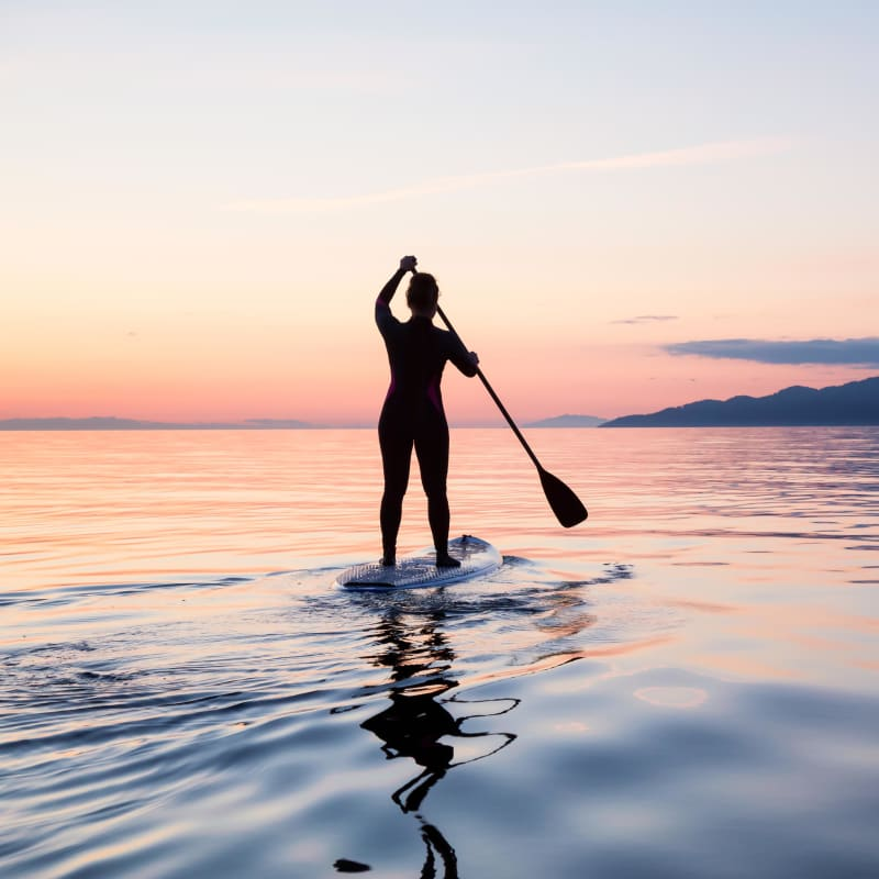 Resident paddleboarding at sunset near Portside Ventura Harbor in Ventura, California