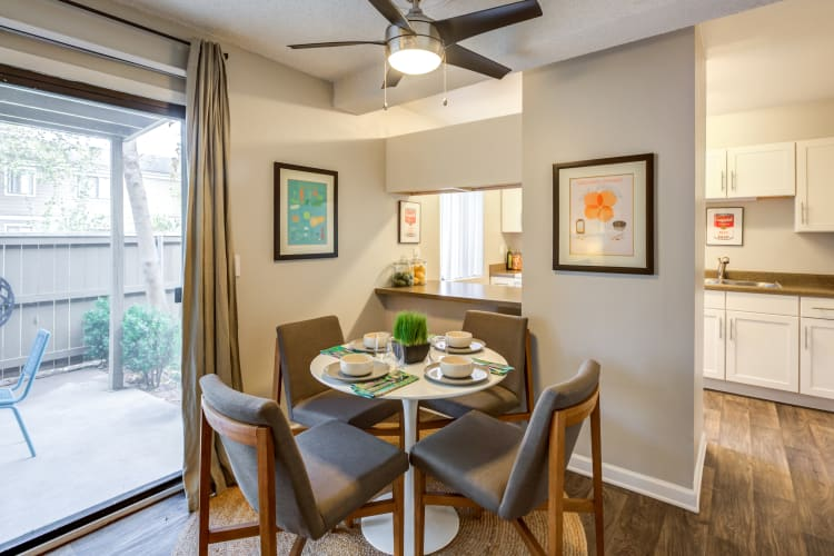 Dining area with a ceiling fan in a model home at The Ranch at Bear Creek Apartments & Townhomes in Lakewood, Colorado