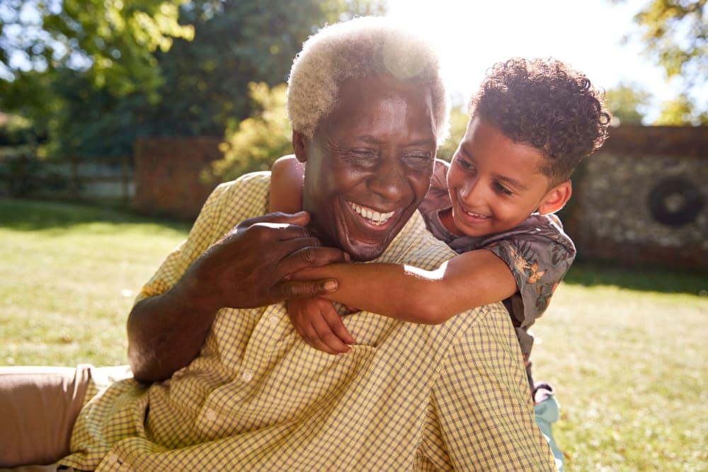 Resident enjoying visit with grandchild at Courtyard Estates at Cedar Pointe in Pleasant Hill, Iowa.