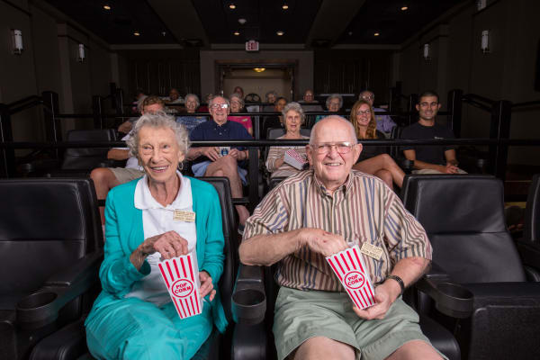 Residents enjoying popcorn while watching a film in the onsite movie theater at Ashton Gardens Gracious Retirement Living in Portland, Maine