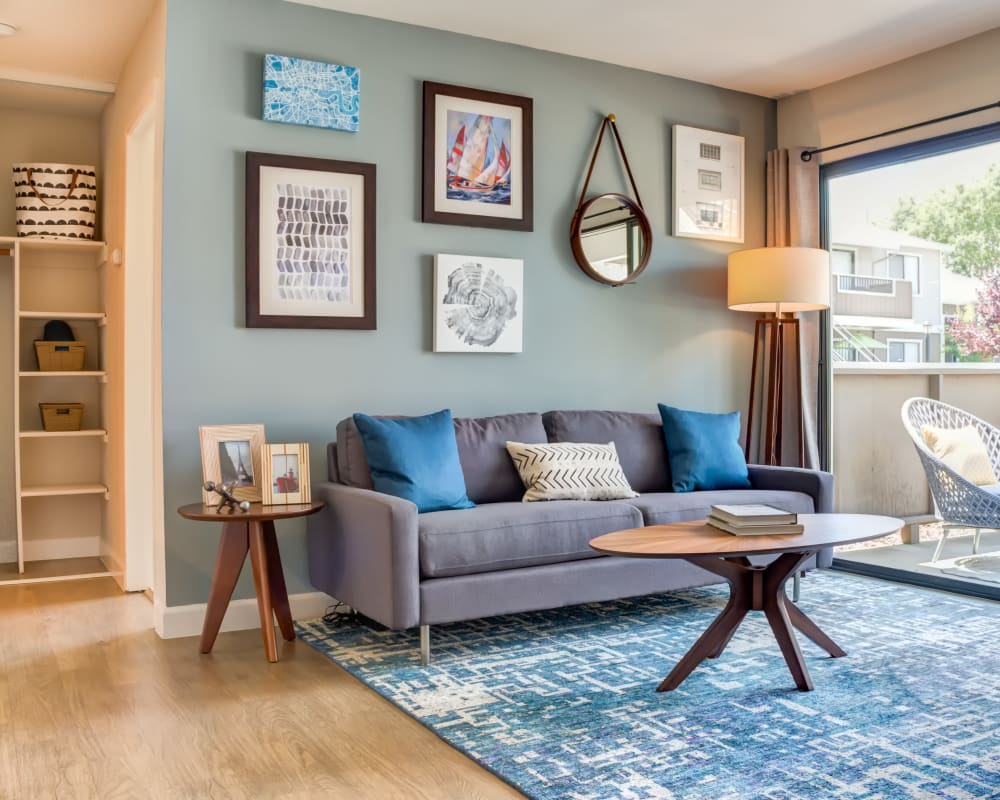 Cozy and well-furnished living space with an accent wall and view of the private balcony outside a model home at Sofi Berryessa in San Jose, California