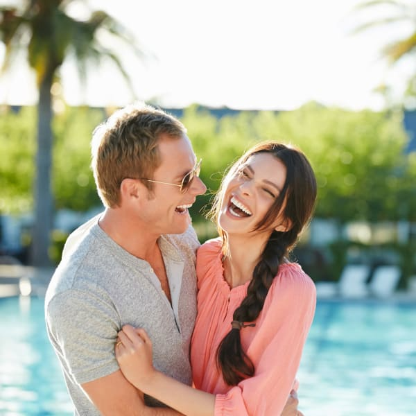 Couple enjoy the sundeck at the pool at Christopher Todd Communities On Greenway in Surprise, Arizona