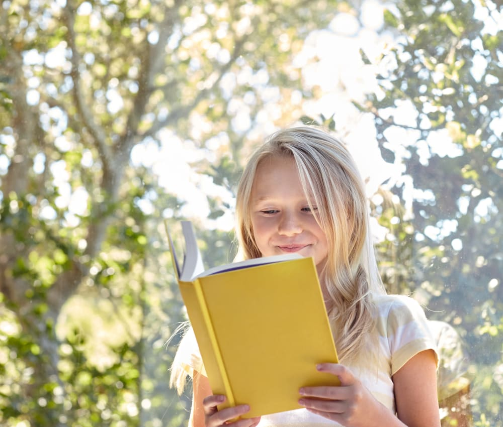 Resident child reading a book in her new home at Waterstone Fremont in Fremont, California