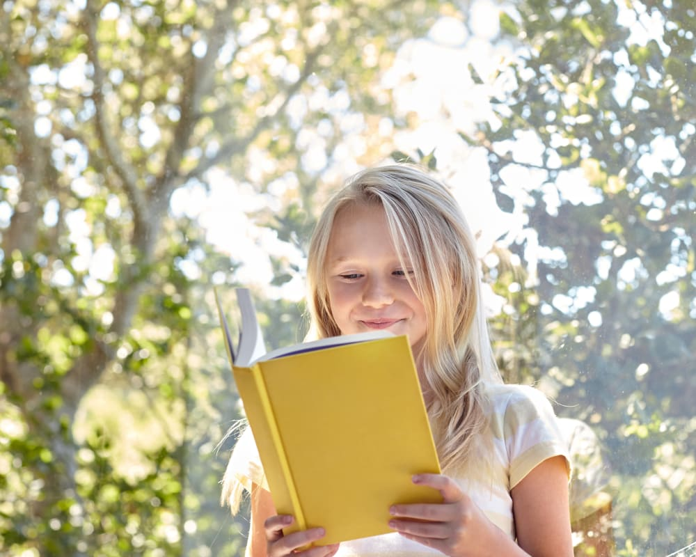 Resident child reading a book outside her new home on another beautiful day at Sofi Canyon Hills in San Diego, California