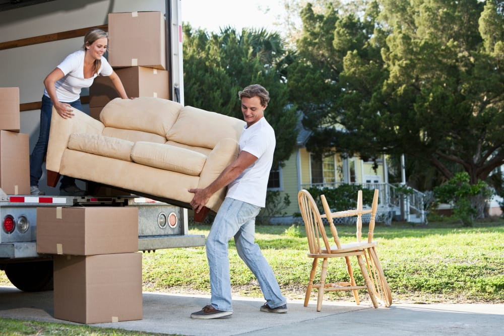 A couple lifting a couch out of a truck at Wheeler Road Self Storage in Augusta, Georgia