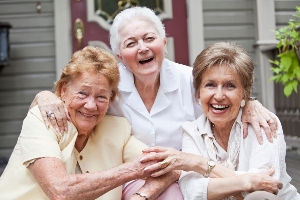 Three senior ladies laughing and hugging