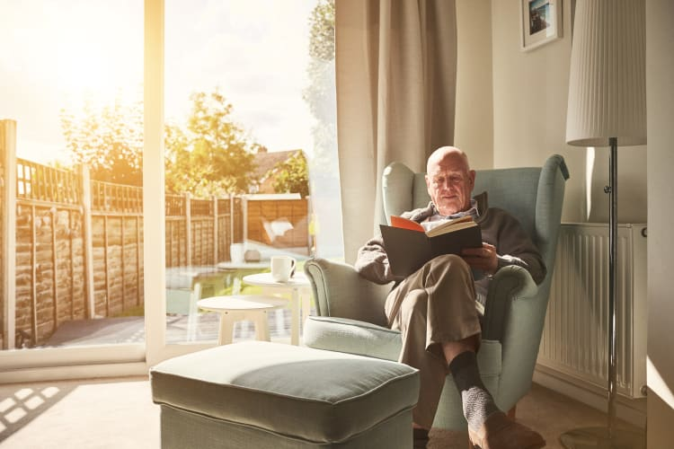 A resident reading a book in his apartment at The Harmony Collection at Roanoke - Independent Living in Roanoke, Virginia