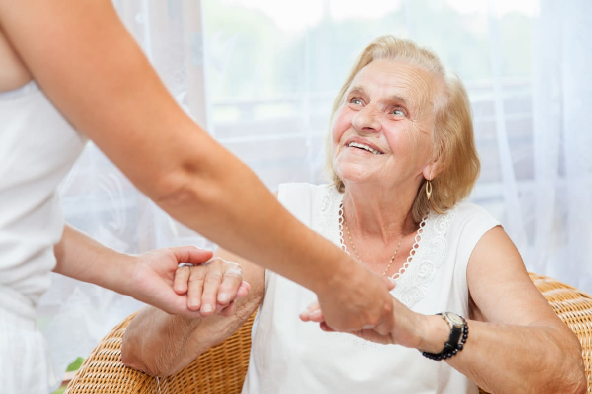 A caretaker holding a resident's hands at Keystone Place at Naples Preserve in Naples, Florida