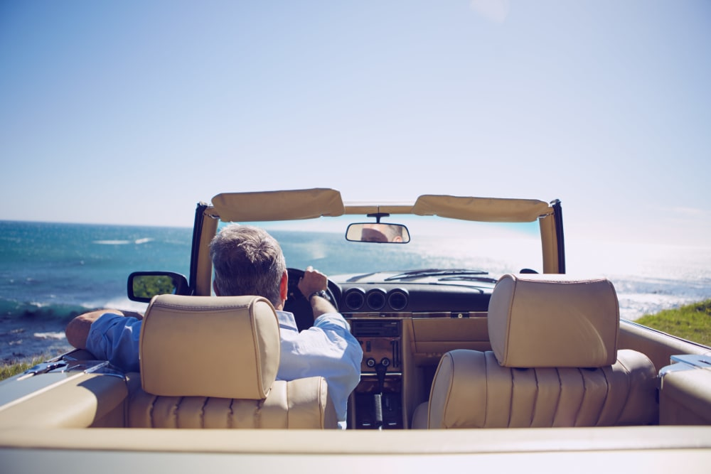 A gentleman in a convertible car looking at the ocean at Elegance Living, LLC in Baltimore, Maryland