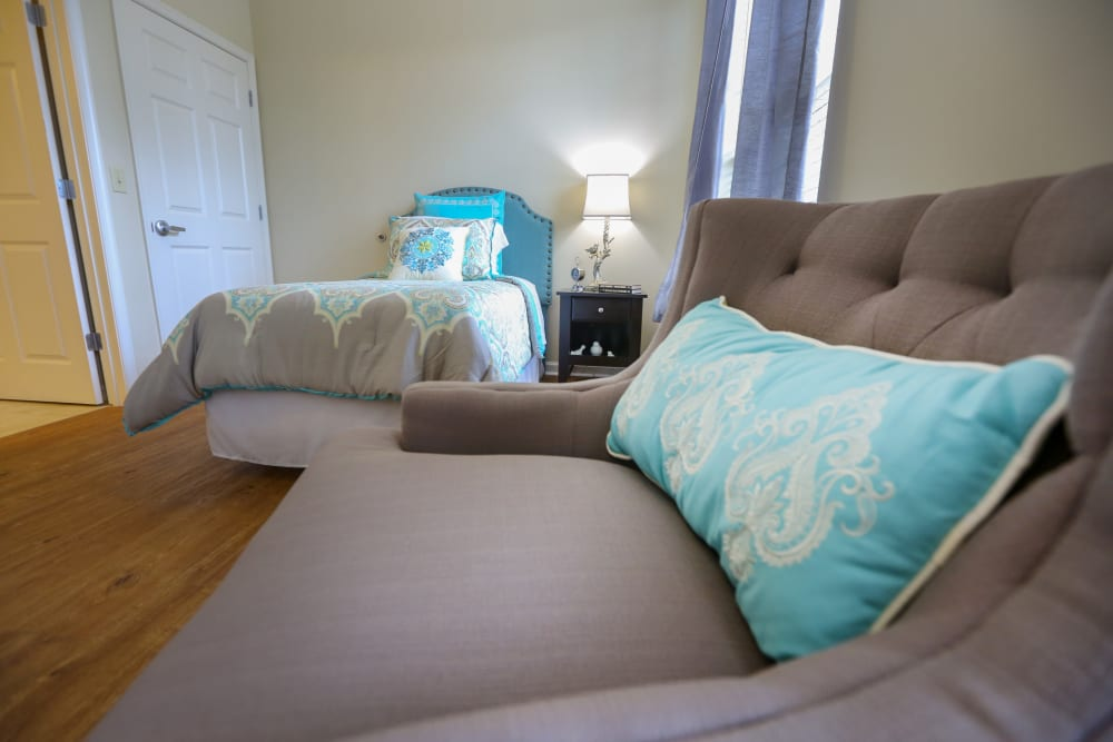 An armchair and bed in an apartment at Harmony at Eastchase in Montgomery, Alabama