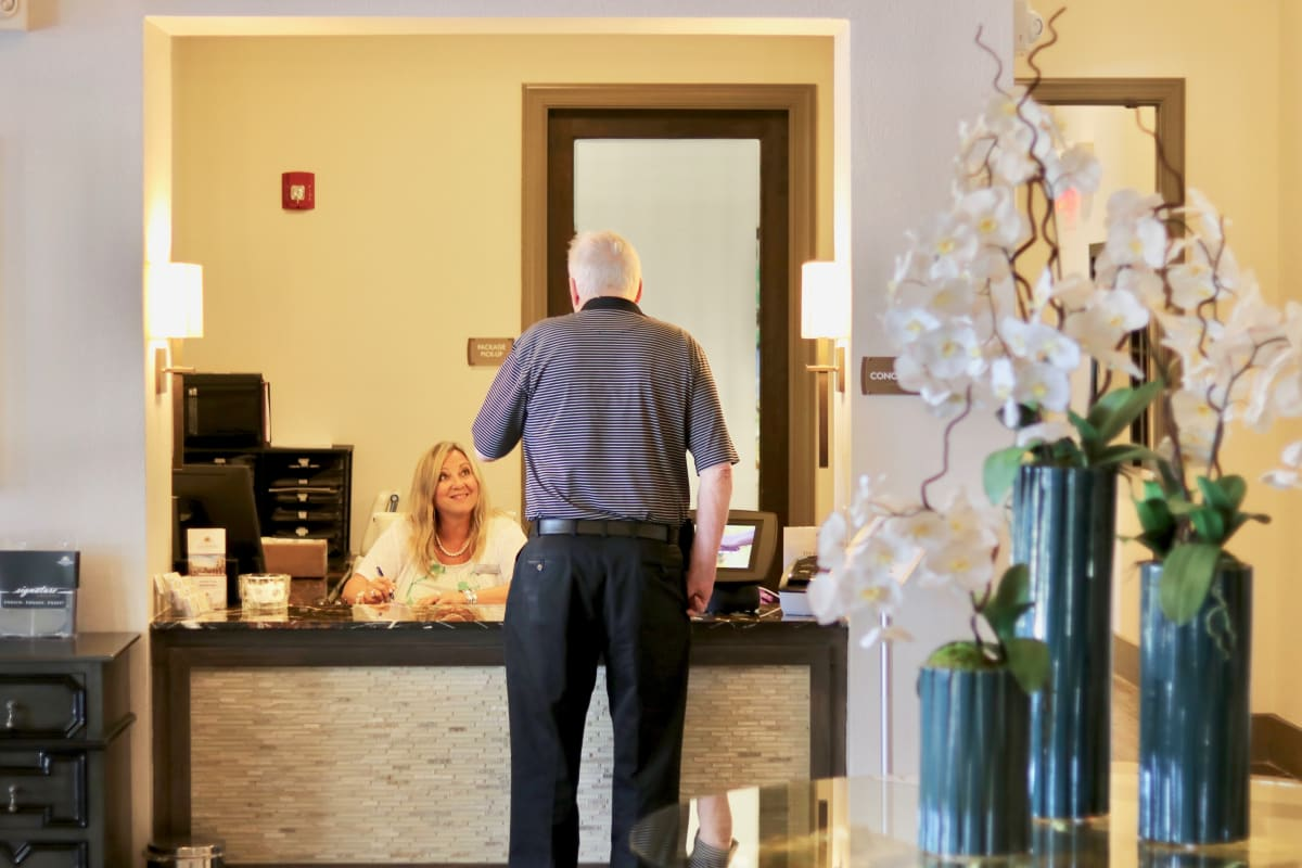 Resident at the front desk of Watermere at Flower Mound in Flower Mound, Texas