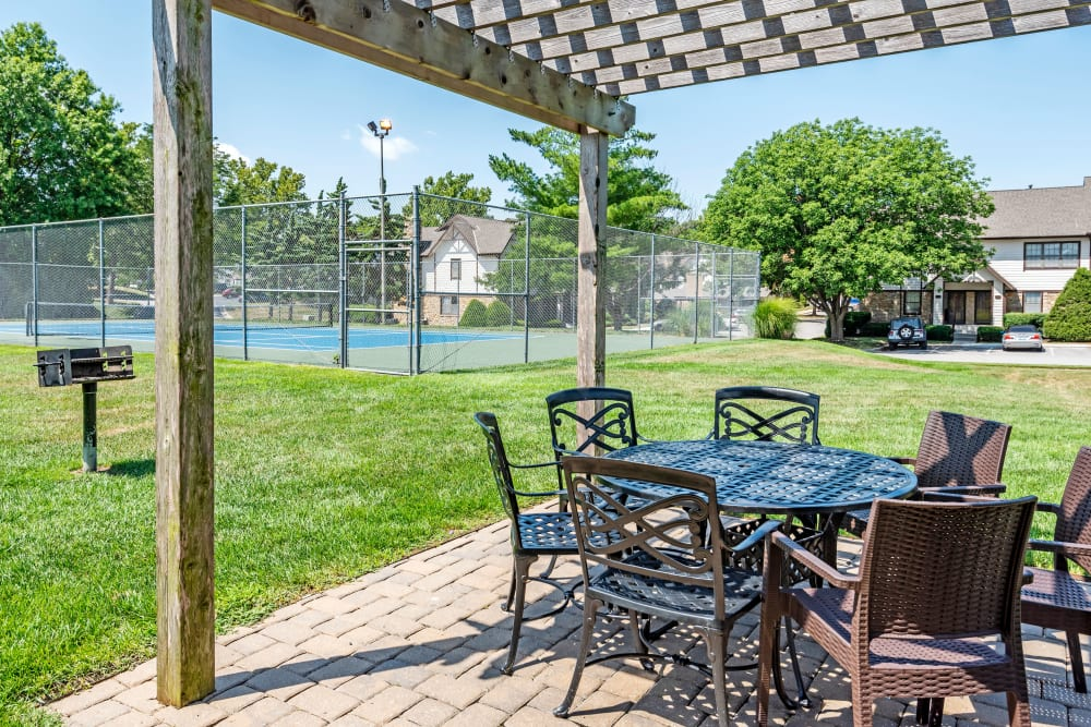 Barbecue area with pergola and grills at Coach House Apartments in Kansas City, Missouri
