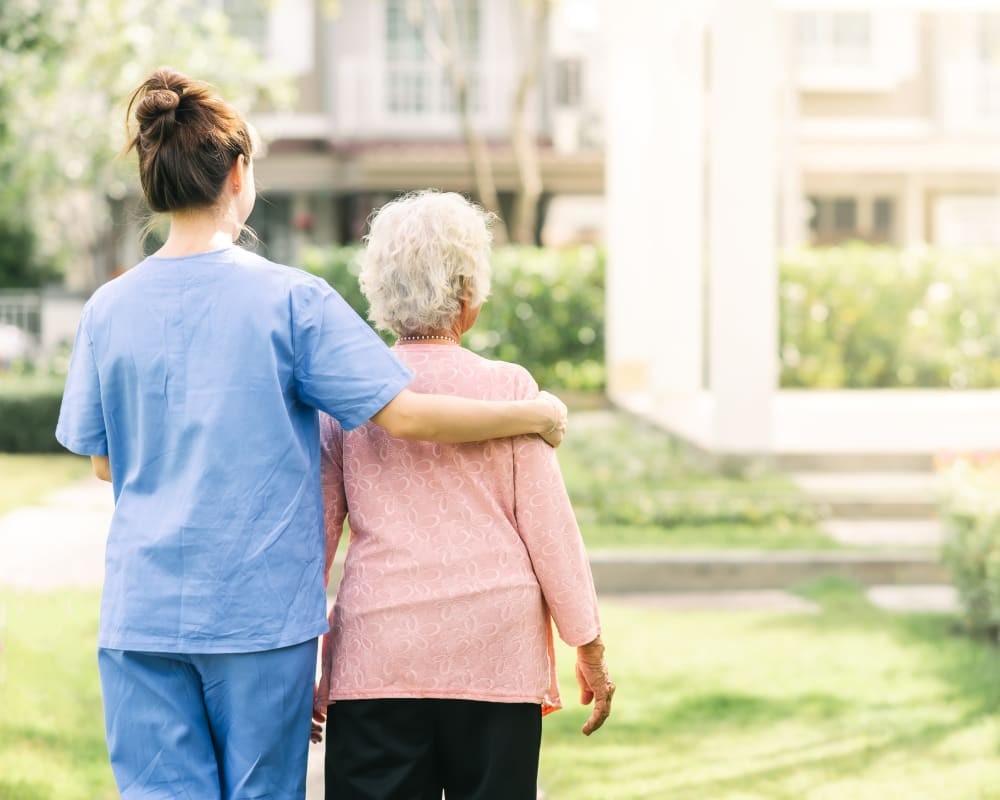 Resident and staff walking together at Country Meadow Place in Mason City, Iowa.