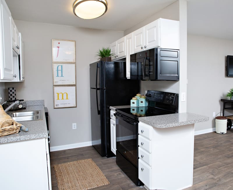 A kitchen with black appliances in a model home at 7029 West in Greensboro, North Carolina