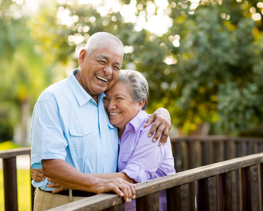 Resident couple hugging while standing on a bridge outside near Edencrest at Beaverdale in Des Moines, Iowa.