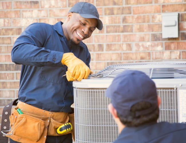 Employees working on an air conditioning unit outside another property managed by American Property Management in Bellevue, Washington
