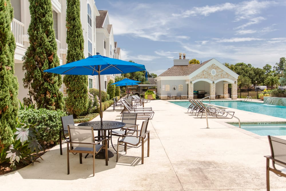Patio tables and lounge seating by the pool at Grand Parkway in Katy,TX