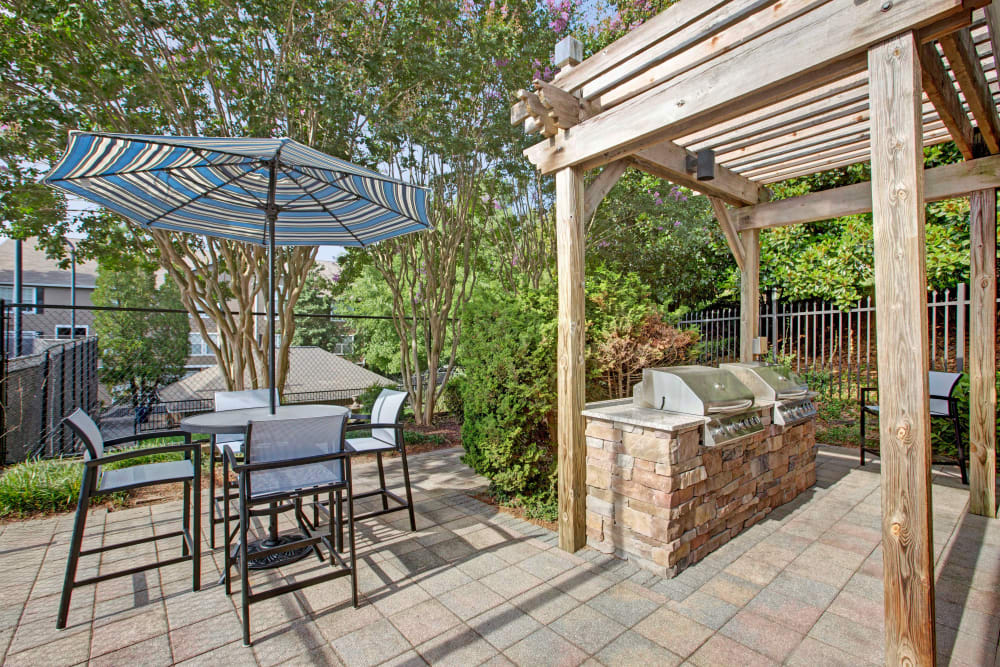 Community outdoor patio area with BBQ at Avia at North Springs in Atlanta, Georgia