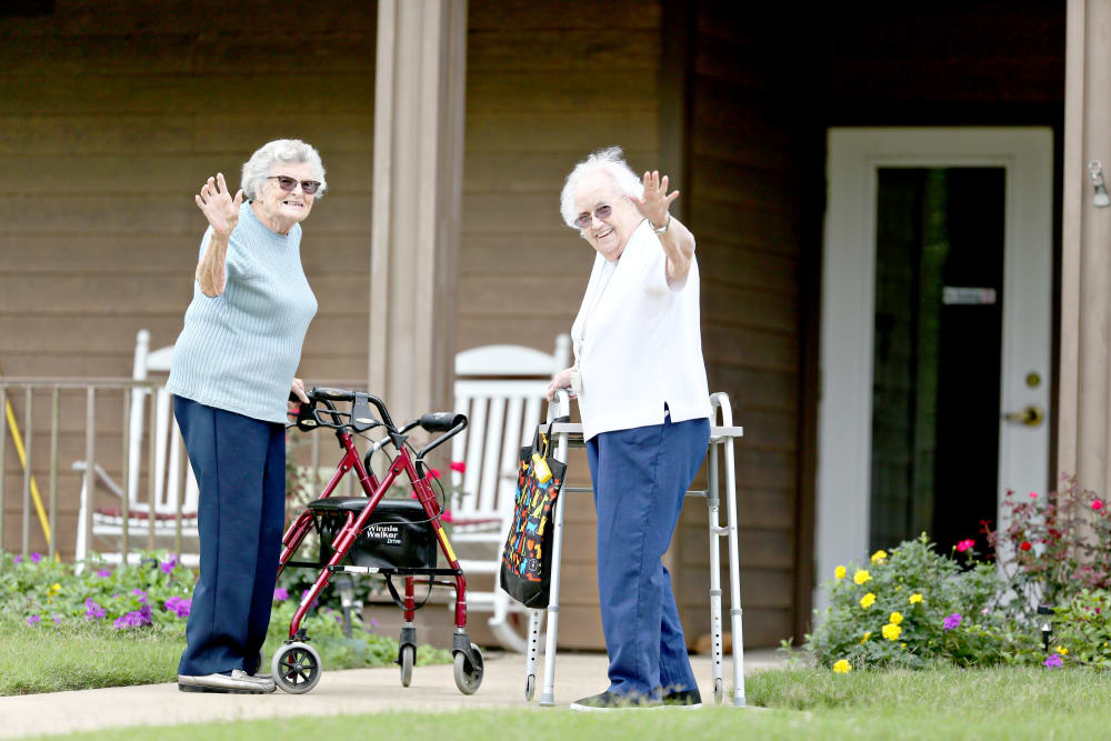 Two residents waving hello on their walk at Providence Assisted Living in Clarksville, Arkansas.