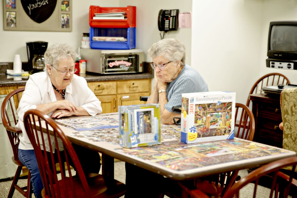 Two residents putting together a puzzle at Providence Assisted Living in Clarksville, Arkansas.