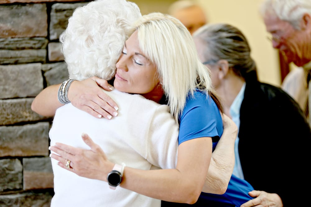 Staff member and resident hugging at Providence Assisted Living in Clarksville, Arkansas.
