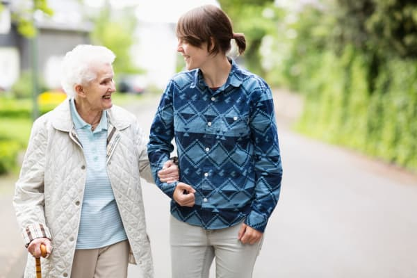 Resident going on walk with caretaker at Pine Grove Crossing in Parker, Colorado