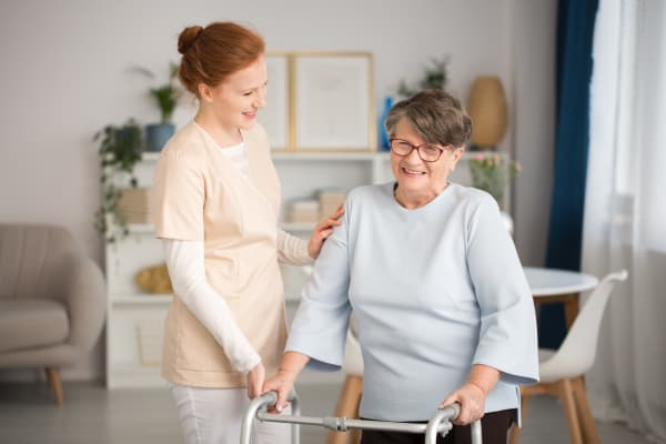 A caretaker assisting a resident with her walker at Harmony Senior Services in Charleston, South Carolina