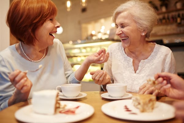 Two senior women laughing over a drink at Clearwater at Riverpark in Oxnard,