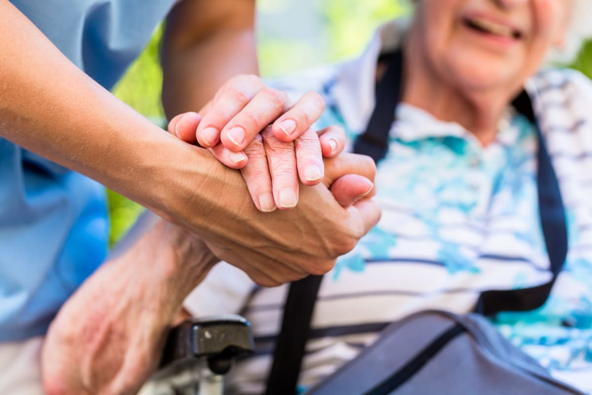 A resident holding hands with a caretaker at Keystone Place at Richland Creek in O'Fallon, Illinois
