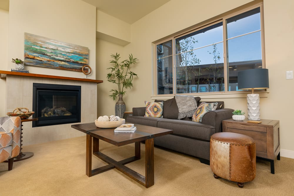 An apartment living room with a fireplace at Touchmark at Fairway Village in Vancouver, Washington