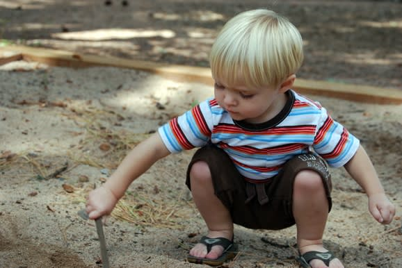 A child playing with a stick in the dirt.