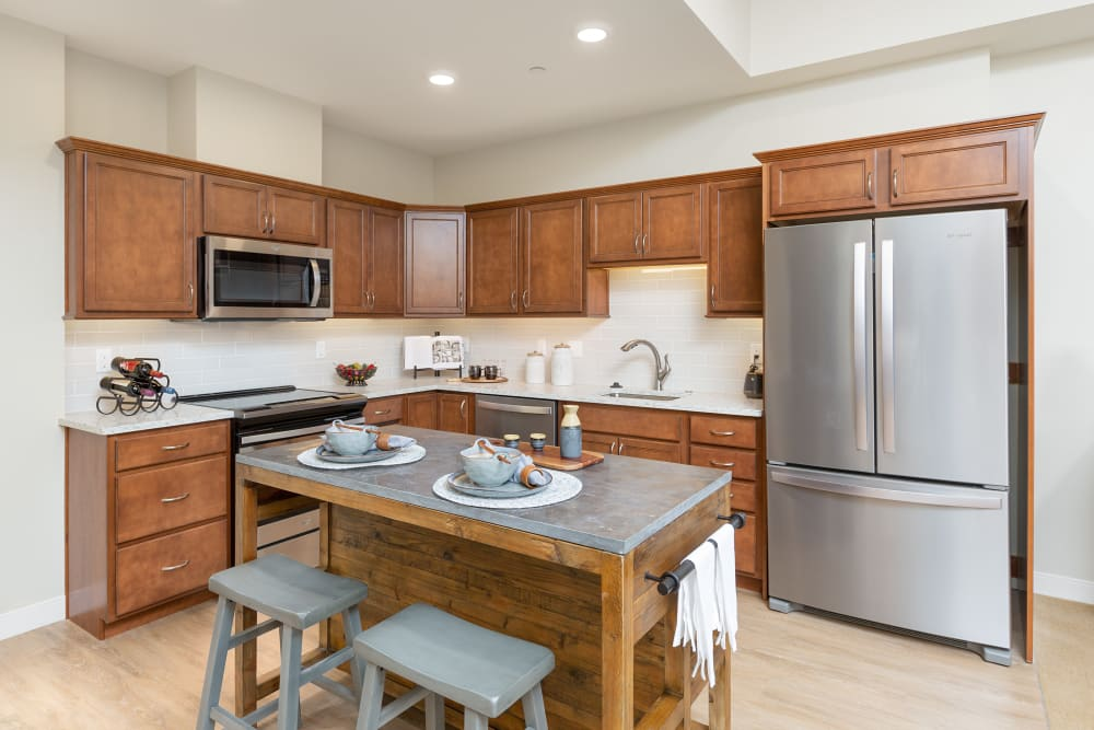 An apartment kitchen with an island at Touchmark at Fairway Village in Vancouver, Washington
