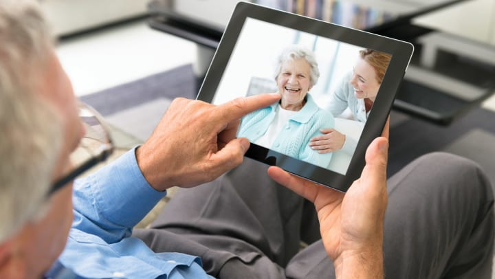 Elderly man talking to friend on iPad